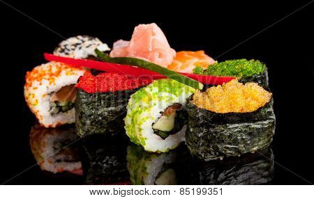Delicious sushi rolls served on black table