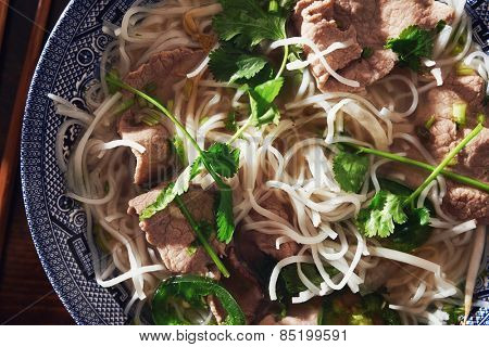 close up top down photo of a bowl of pho with beef slices