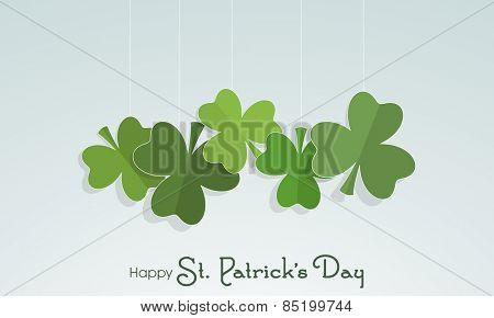 Paper folded shamrock leaves hanging on blue background for Happy St. Patrick's Day celebration.