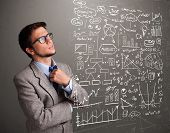 picture of anal  - Attractive young man looking at stock market graphs and symbols - JPG