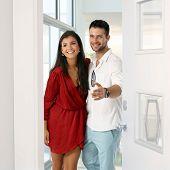 foto of gesture  - Happy young attractive caucasian couple standing in new home doorway - JPG