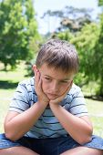 pic of sad boy  - Little boy feeling sad in the park on a sunny day - JPG