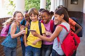 image of pupils  - Cute pupils using mobile phone at the elementary school - JPG