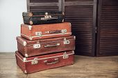 stock photo of yesteryear  - Old suitcases on a background of dark wood screen - JPG