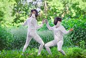 picture of rapier  - Two rapier fencer women fighting over beautiful nature park background - JPG