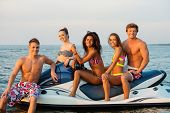 stock photo of ski boat  - Group of happy multi ethnic friends sitting on a jet ski - JPG
