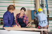 stock photo of carpenter  - Portrait of female carpenter holding digital tablet while standing by colleague in workshop - JPG