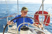 picture of yachts  - Young man skipper at the helm controls sailing yacht - JPG