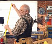 stock photo of handyman  - Happy casual senior handyman measuring with folding ruler at workshop - JPG