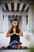 stock photo of yoga mat  - Woman practicing yoga in a urban background - JPG