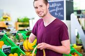 picture of supermarket  - Man selecting bananas while grocery shopping in organic supermarket  - JPG