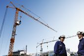 picture of worker  - two site workers inside construction plant mobile cranes in background - JPG