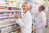 picture of coat  - Pharmacists in lab coat looking at medicine in the pharmacy - JPG