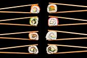 foto of chopsticks  - Set of sushi pieces in chopsticks - JPG