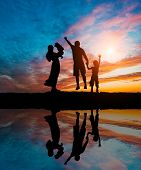 picture of time flies  - Silhouettes of happy parents having good time with their little children on the seacoast - JPG