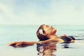 picture of bathing  - Luxury resort woman relaxing in infinity swim pool - JPG
