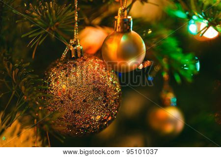 Golden Bauble In Christmas Tree Surrounded By Colorful Lights