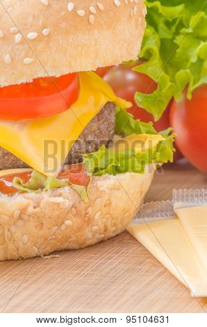 Tasty cheeseburger with lettuce beef double cheese and ketchup. Macro with shallow focus.