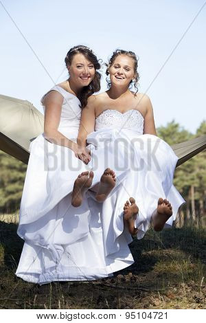 Two Brides In Hammock Against Blue Sky With Forest Background