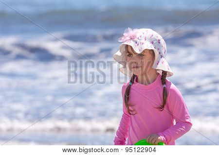 little girl at a beach wearing long sleeve shirt and hat
