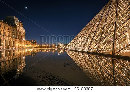 Reflection of Louvre pyramid shines at dusk.