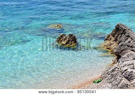 Beach With Clear Water And Green Slippers
