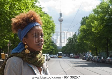 Head Shot Of Young Curly Woman In Berlin In Front Of The Tv Tower.