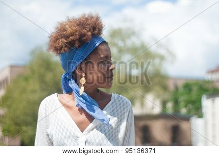Head Shot Of Young Afro American Curly Woman In Urban Surrounding .head Shot Of Young Afro American