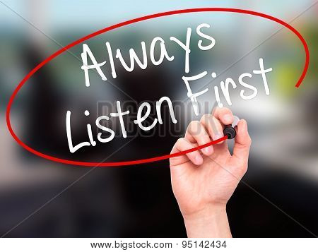 Man Hand writing Always Listen First with black marker on visual screen.
