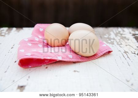 Eggs on tablecloth over wooden background
