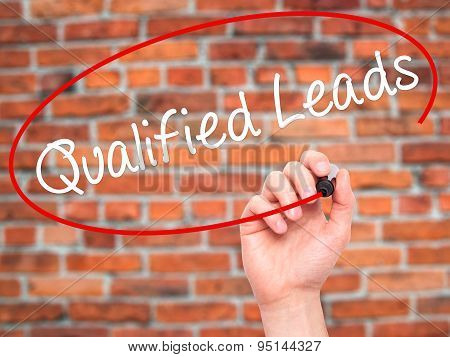 Man Hand writing Qualified Leads with black marker on visual screen.