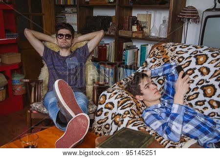 Young man looking smartphone lying and friend relaxing in rocking chair