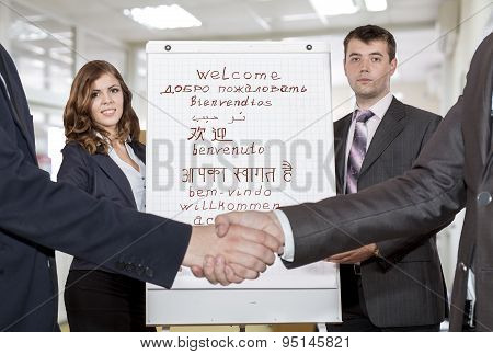 Two young corporate trainers welcome participants of the training
