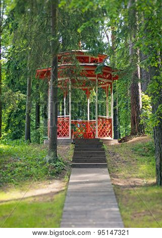 Red Wooden Gazebo In The Forest.