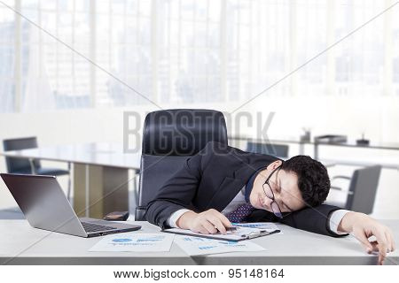 Overworked Worker Sleeping At Workplace