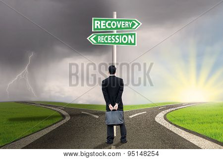 Person With Signpost Of Recession And Recovery Finance