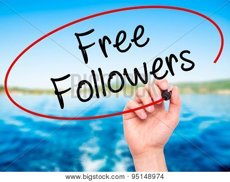 Man Hand writing Free Followers with black marker on visual screen.
