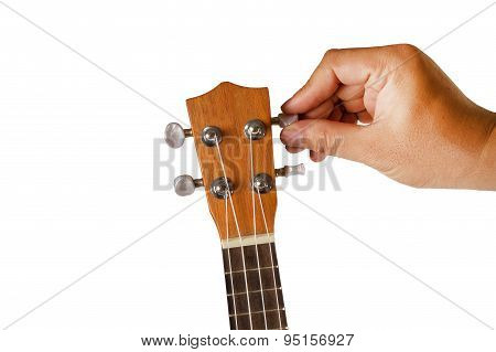 Hand tuning ukulele on white background