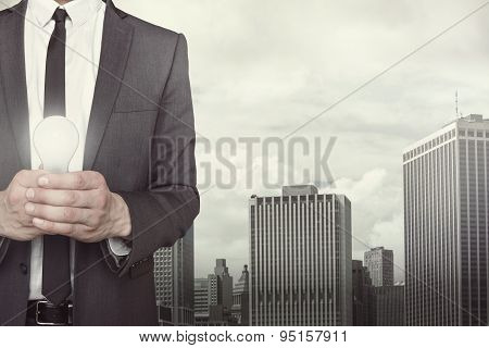 Businessman holding light bulb in hands