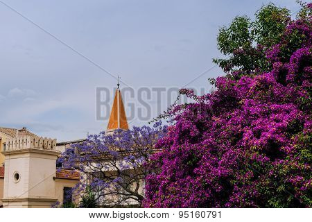 Old mediterranean church and houses in flowers of bougainvillea