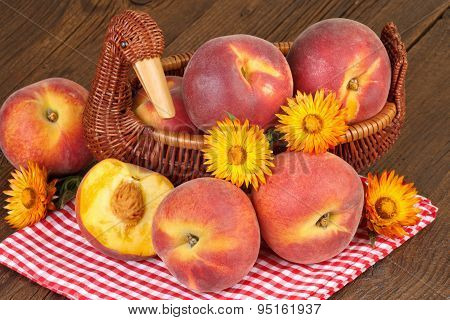 Peaches in vintage basket on checkered red tablecloth