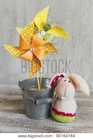 Homemade Paper Pinwheel And The Easter Bunny On A Light Wooden Background