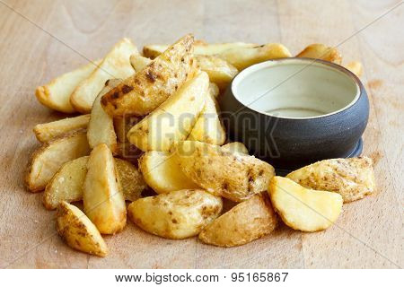 Heap Of Fried Potato Wedges On Wood Board With Rustic Dip Bowl.