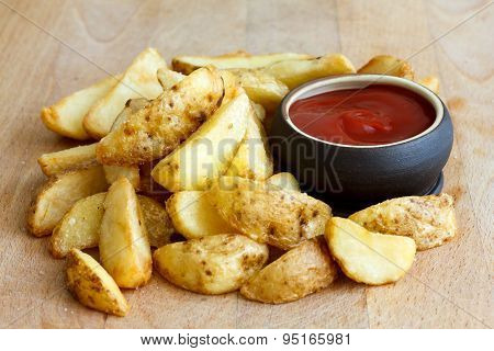 Heap Of Fried Potato Wedges On Wood Board With Ketchup Dip In Bowl.