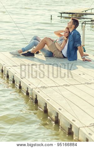 Couple in love sitting on the pier embrace