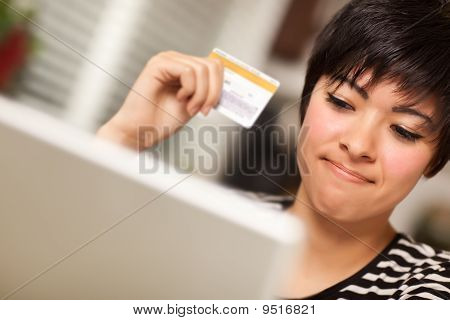 Smiling Multiethnic Woman Holding Credit Card Using Laptop