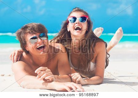 Closeup of happy young caucasian couple in sunglasses smiling at beach lying on sand