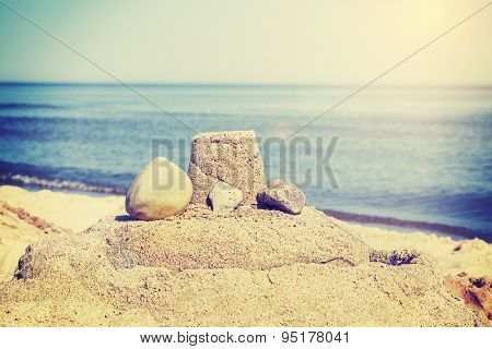 Vintage Retro Toned Simple Sandcastle On A Beach, Summer Holidays Concept.