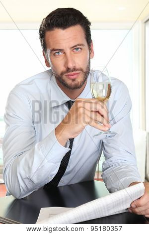 handsome man drinking a glass of sparkling wine white sitting at the bar with newspaper