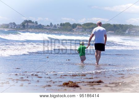 grandfather with his grandson walking on a beach